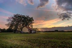 Isoloated hus i fältet på solnedgången med molnigt royaltyfri fotografi