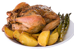 Isoloated roasted whole chicken on a plate. Roasted whole chicken on a plate with fried potato and asparagus Stock Photography