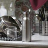 Isolou a garrafa inoxidável com utensílios e afundam o fundo da cozinha imagem de stock