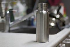 Isolou a garrafa inoxidável com utensílios e afundam o fundo da cozinha fotografia de stock royalty free