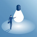 Isometric businessman and idea. Businessman standing in a circle of light from a large light bulb as a symbol of new ideas. An employee found the idea and Stock Photo