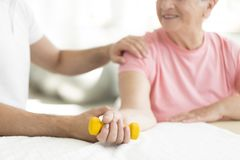 Isometric exercise session. Senior patient committed to an active, isometric exercise session with her physiotherapist at nursing home Stock Images