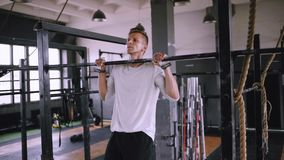 Pulls up on bar in gym. Isomtric pull-ups to be fit. Best exercises in the gym. Strong middle-aged man pulls up on bar in gym and stayed up, static load muscles stock video footage