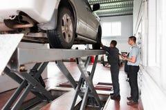 Ispezione del sistema di sospensione dell'automobile all'officina fotografia stock
