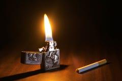 Isqueiro e um cigarro em um assoalho de madeira Fotos de Stock