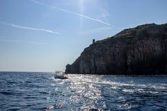 Isquiones, barco que va hacia la puesta del sol fotografía de archivo libre de regalías