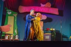 Israël, bier-Sheva - Actoren het theater van kinderen op het stadium in een blauwe en gele regenjas 2015 royalty-vrije stock afbeelding