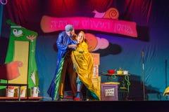 Israël, bier-Sheva - Actoren het theater van kinderen op het stadium in een blauwe en gele regenjas 2015 Stock Afbeelding