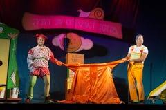 Israël, bier-Sheva - Twee actoren op het stadium worden getrokken in verschillende richtingen oranje regenjas Royalty-vrije Stock Foto's