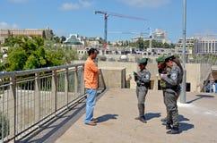 Israel Border Police. JERUSALEM - MAY 05 2015:Israeli border patrol policewomen checking Arab man ID and work permits.The force securing Israel borders and Stock Photos