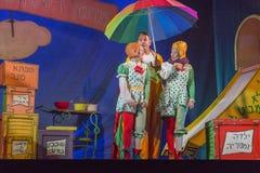 Israel, cerveja-Sheva, Negev - dois atrizes e atores do teatro das crianças na fase com um grande guarda-chuva, 2015 imagem de stock royalty free