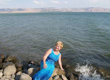 israel Die Frau von durchschnittlichen Jahren auf der Bank vom See Kinerets lizenzfreie stockfotografie