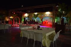 Israel, Dimona,Hall of celebrations Mor 2018 - Hall of celebrations with tables and chairs at night. Hall of celebrations with tables and chairs at night Stock Photo