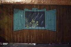 Israel, Dimona, 2018 - uma cerca de madeira e uma janela pintada com obturadores e um ramalhete das flores na noite imagens de stock royalty free
