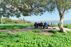 Israel. - February 17.2017. A group of pilgrims rests on the shore of the Sea of Galilee Stock Photo