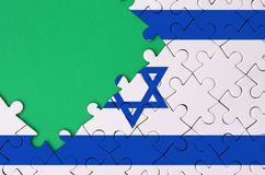Israel flag is depicted on a completed jigsaw puzzle with free green copy space on the left side.  stock illustration