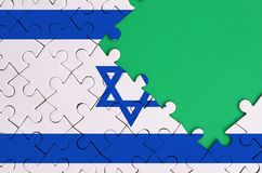 Israel flag is depicted on a completed jigsaw puzzle with free green copy space on the right side.  stock images