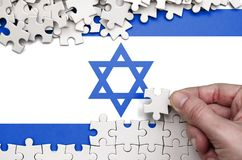 Israel flag is depicted on a table on which the human hand folds a puzzle of white color.  royalty free stock photo