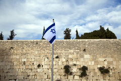 Israel Flag & The Wailing Wall. Israel flag fluttering in the wind in front of the holy Wailing Wall, one of the most sacred places to the Jewish people royalty free stock photos
