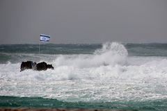 Israel flag in a stormy sea. Israel flag on a rock in a stormy sea royalty free stock photos