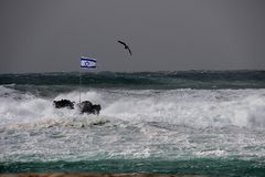 Israel flag in a stormy sea. Israel flag on a rock in a stormy sea royalty free stock photography