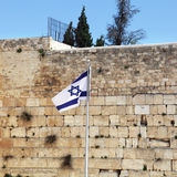 Israel Flag and The Wailing Wall. Israel flag fluttering in the wind in front of the holy Wailing Wall, one of the most sacred places to the Jewish people royalty free stock photos