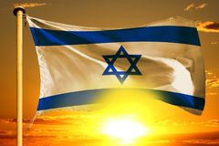 Israel flag weaving on the beautiful orange sunset with clouds background. Israel flag weaving on the beautiful orange sunset background royalty free stock images