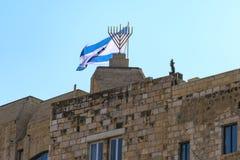 Israel Jerusalem, den israeliska flaggan och denbeväpnade ljusstaken som fotograferas från bottenvåningen nära den att jämra sig  arkivfoto