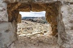 Israel Jerusalem, der Mount Zion, eine einzigartige Ansicht durch einen Felsen zur alten Stadt, mit vielen Gräbern im Vordergrund Lizenzfreie Stockfotos