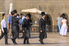 Israel Jerusalem, klagovisa-väggen 15th September 2017 tre ortodoxa judiska män går bland turisterna, på jordningen av wailinen Arkivfoto