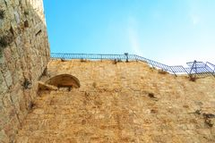 Israel Jerusalem, view of the old city wall, photographed from below with the background of the fence on the wall, against a brigh Stock Images