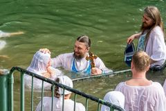 Israel / Jordan River - 03.26.2016: Christian pilgrims during the baptism ceremony on the Jordan River in Northern Israel the stock photo