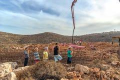 Israel Judea öken Oktober 24, 2015 Judisk nybyggarebarnklocka som det olagligt upptagna landet i bosättningen med agricul royaltyfri fotografi