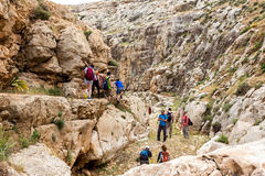 ISRAEL, NEGEV DESERT - APRIL 07, 2016: people go through rocky desert. ISRAEL, NEGEV DESERT Stock Photo