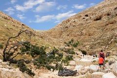 ISRAEL, NEGEV DESERT - APRIL 07, 2016: people go through rocky desert. ISRAEL, NEGEV DESERT Royalty Free Stock Images