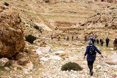ISRAEL, NEGEV DESERT - APRIL 07, 2016: people go through rocky desert. ISRAEL, NEGEV DESERT Stock Images