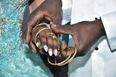 Israel, Negev, 2016 - Hände enthäuteten Braut und Bräutigam tauschte Goldringe aus Braut in einem Türkiskleid Lizenzfreie Stockbilder