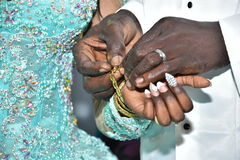 Israel, Negev, 2016 - Hands skinned bride and groom exchanged gold rings. Bride in a turquoise dress Royalty Free Stock Images