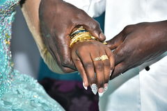 Israel, Negev, 2016 - Hands skinned bride and groom exchanged gold rings. Bride in a turquoise dress Stock Photos