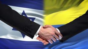 Israel och Ukraina handskakning, internationell kamratskappolitik, flaggabakgrund stock video