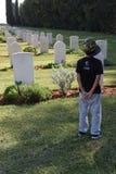 Israel, Ramle, 2018 - um menino em um chapéu está com o o seu de volta ao cemitério fotos de stock royalty free