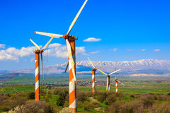 Israel. Some huge modern windmills. Israel. The blossoming Golan heights in a sunny day. Some huge modern windmills. In the distance snow-covered Hermon is seen Stock Photography