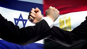 Israel vs Egypt confrontation, countries disagreement, fists on flag background. Stock photo stock photography