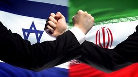 Israel vs Iran confrontation, countries disagreement, fists on flag background. Stock photo stock photo