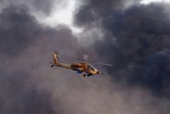 Israeli Air Force Helicopter. SOUTH ISRAEL - JUNE 28: An israeli IAF military AH-64 Apache helicopter in the air  with smoke in the background in southern Israel Stock Images