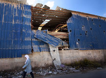 Israeli artillery shots in Palestine. A palestinian girl passes by a factory destroyed by artillery shots from the Israeli army in West Bank stock images
