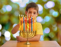 Israeli boy lighting a Hannukah Menorah. An Israeli 8 year old child lighting a Hanukkah Menorah Royalty Free Stock Image