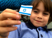 Israeli child holds Israel flag. Israeli child (girl age 5-6) holds small Israel flag during Israel's independents day stock image