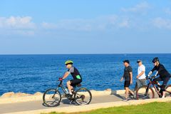 Israeli elderly men ride a bicycle along Tel-Aviv beach. stock image