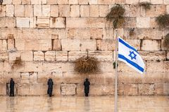 Israeli flag against the western wall on a cloudy day in Jerusalem stock images